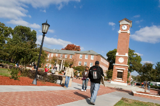 students walking; clock tower; building